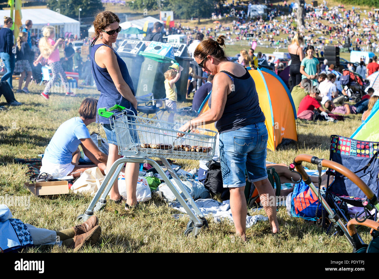Female using a supermarket trolley as a barbecue to cook sausages in the crowd at the Bristol International Balloon Fiesta. Money saving idea. £1 BBQ - Stock Image