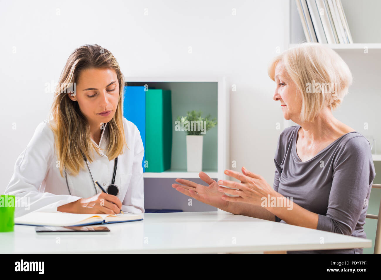 Female doctor and senior woman patient talking in doctor's office. - Stock Image