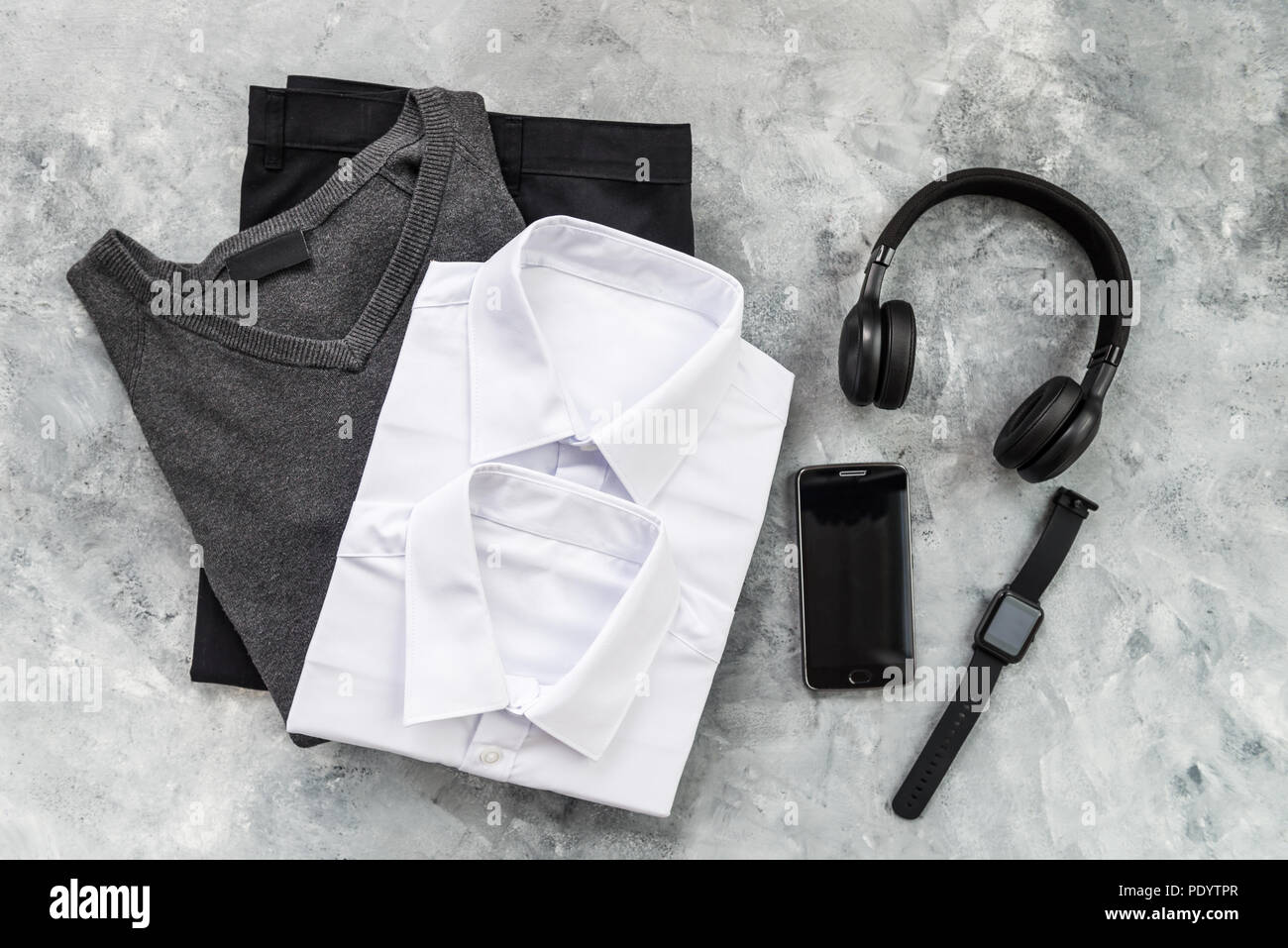 Back to school concept, school uniform such as white shirts and trousers, as well as electronic devices such as smart watch, mobile and headphones on  - Stock Image