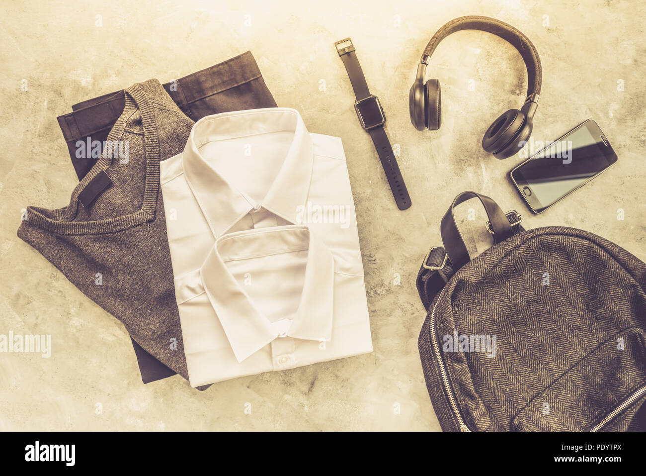 Back to school concept, backpack with school uniform such as white shirts and trousers, as well as electronic devices such as smart watch, mobile and  - Stock Image