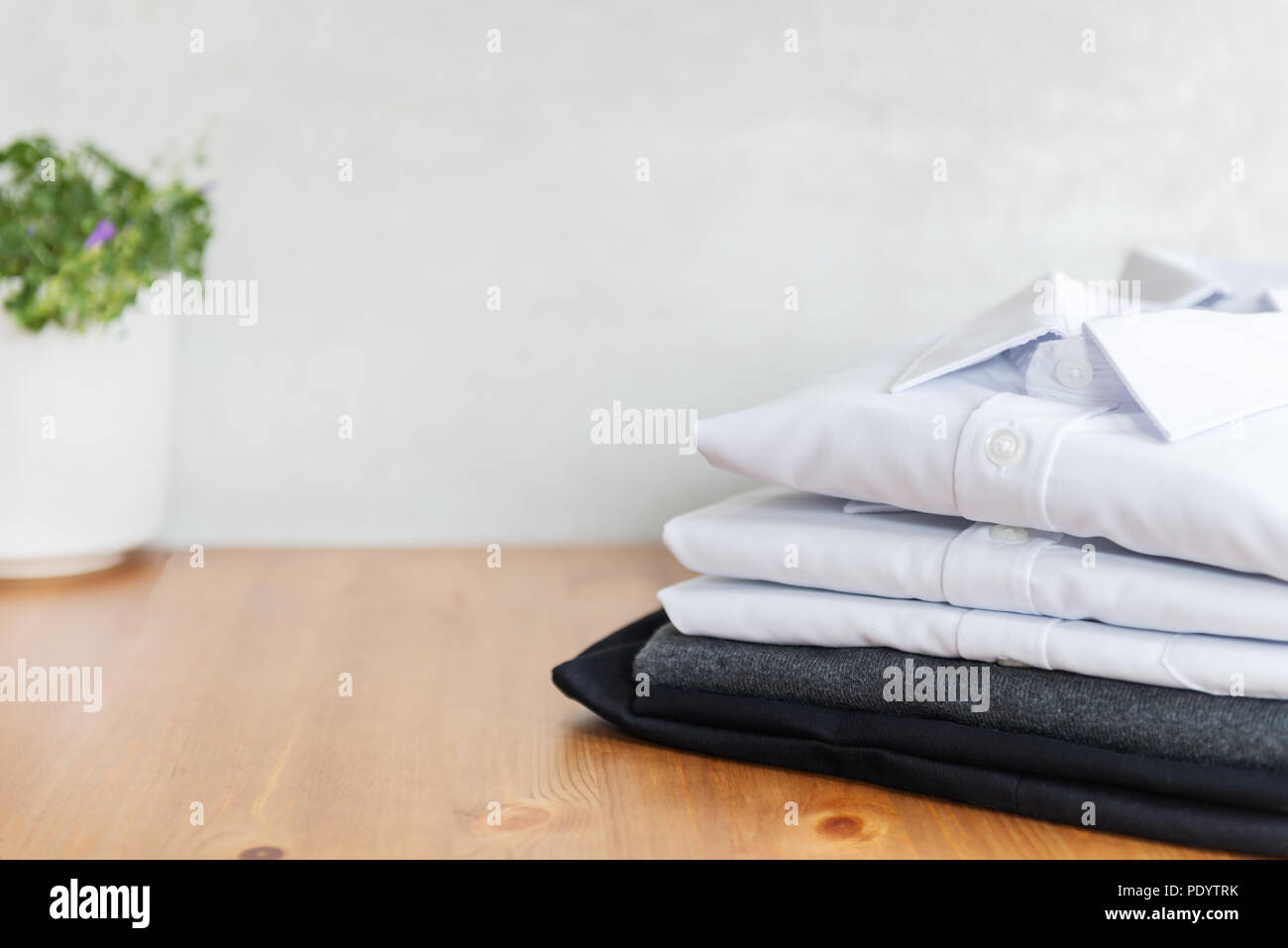 Back to school concept, school uniform such as white shirts, sweater and trousers on the light background - Stock Image