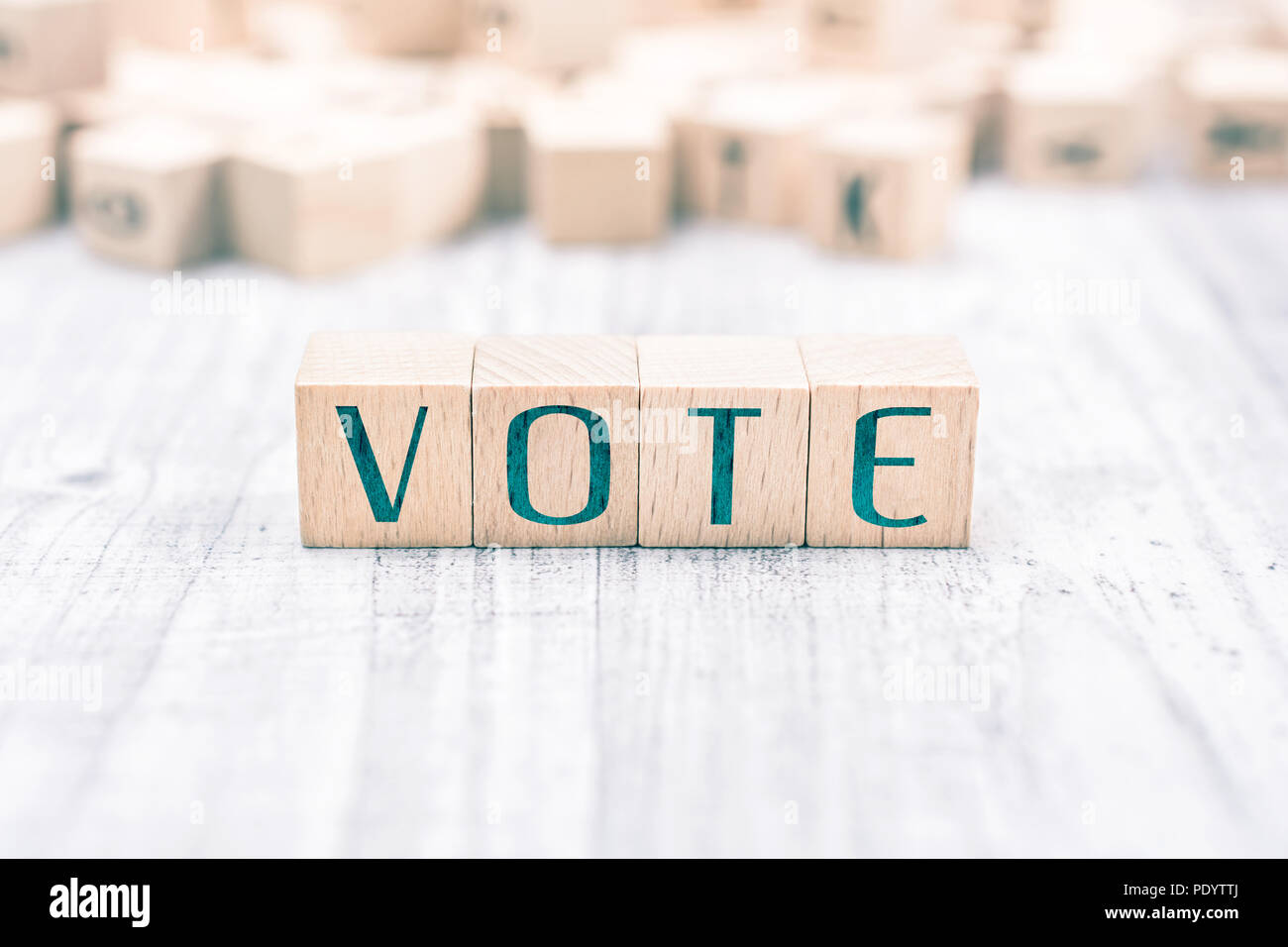 The Word Vote Formed By Wooden Blocks On A White Table, Reminder Concept Stock Photo