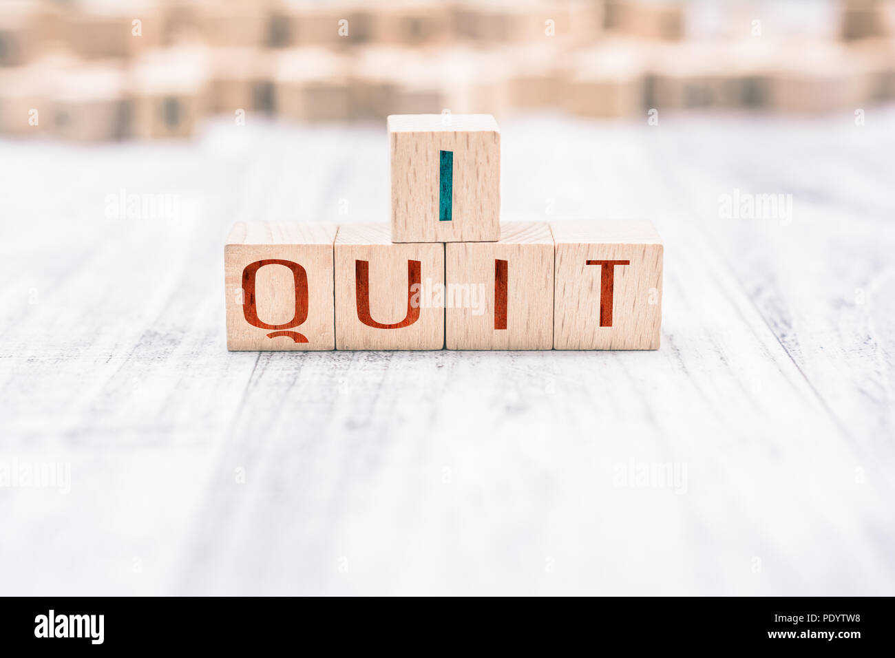 The Words I Quit Formed By Wooden Blocks On A White Table - Stock Image