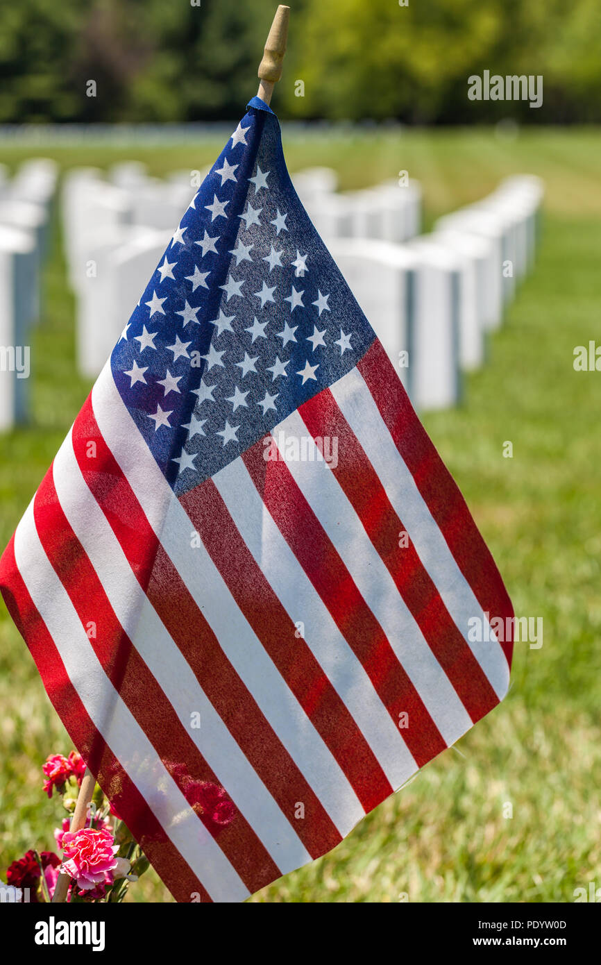 Close up of the United States National flag with white headstones in the background in National cemetery Stock Photo