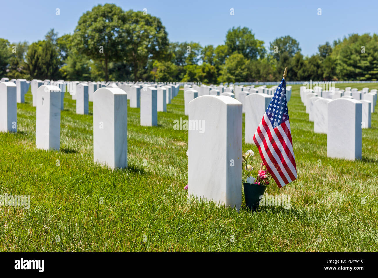 The United States National flag with white headstones in the background in Camp Butler National cemetery Stock Photo
