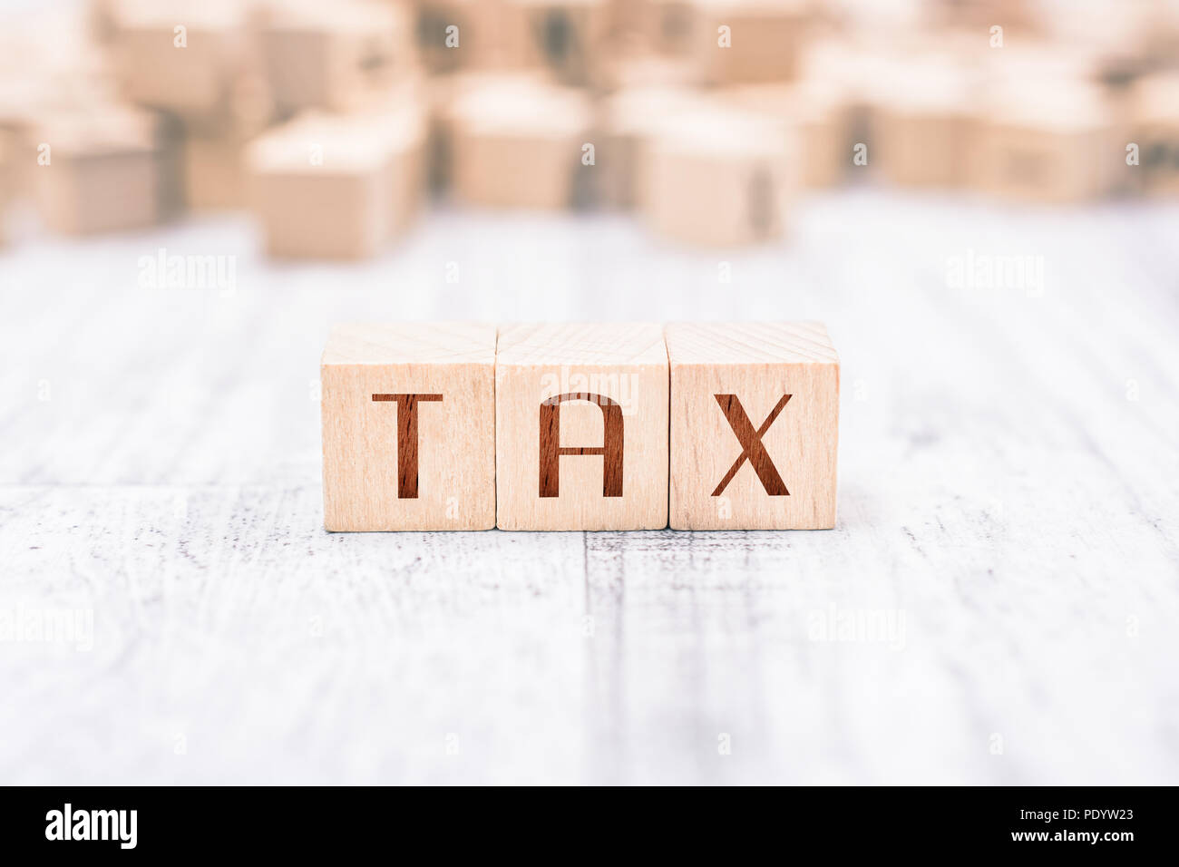 The Word Tax Formed By Wooden Blocks On A White Table, Reminder Concept Stock Photo