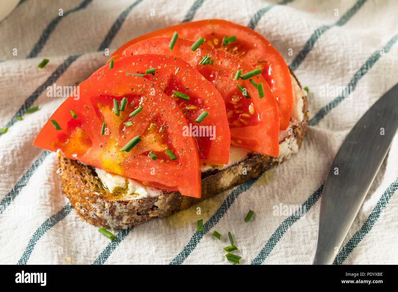 Trendy Homemade Tomato Toast with Goat Cheese and Chives - Stock Image