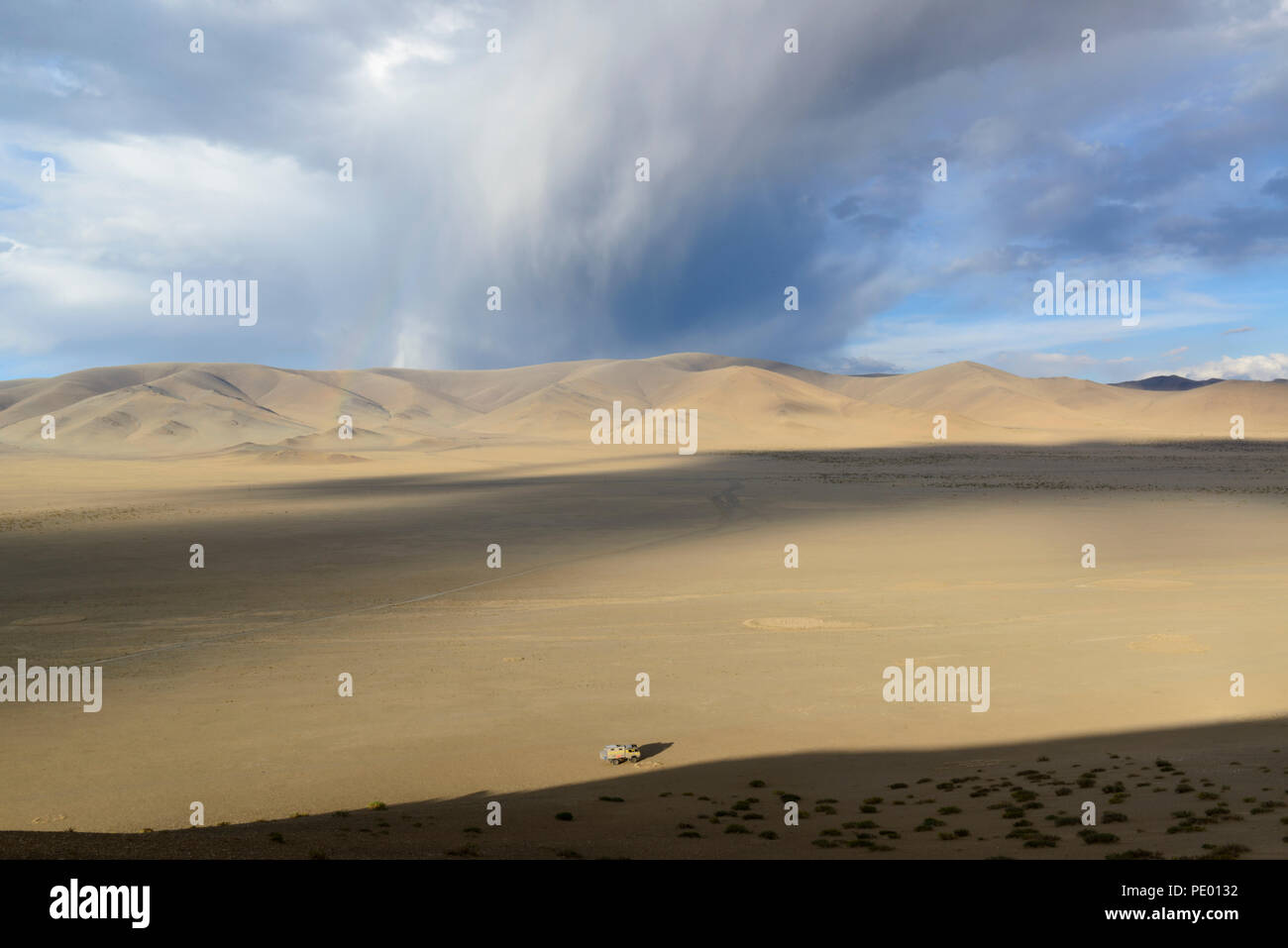 Thunderclouds and starting rainbow on an arid plain of the province Bayan-Ólgii in Mongolia. Overlander truck on foreground - Stock Image