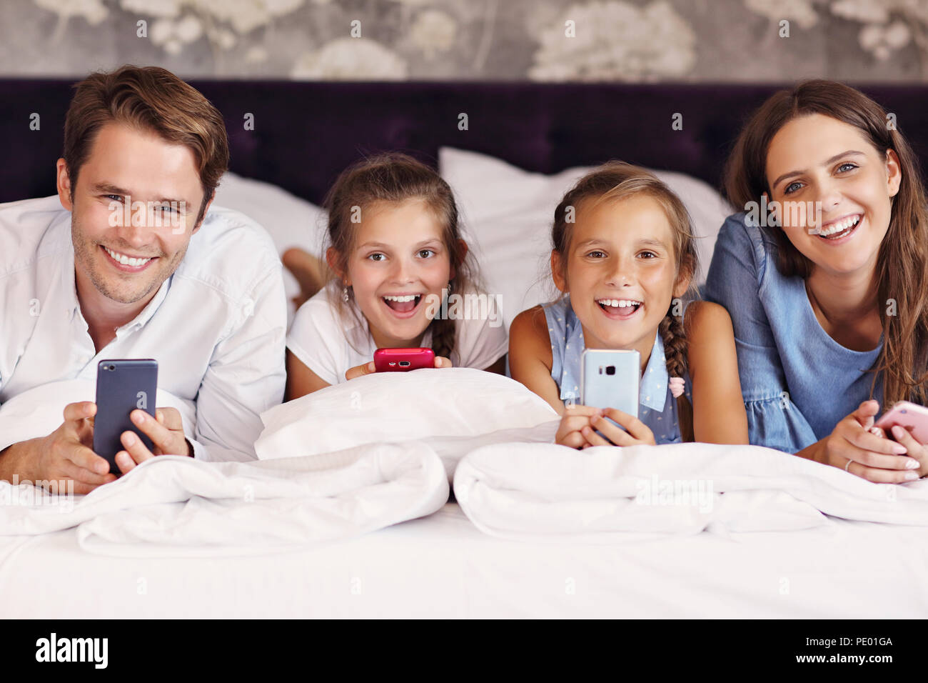 Happy family relaxing in hotel room - Stock Image