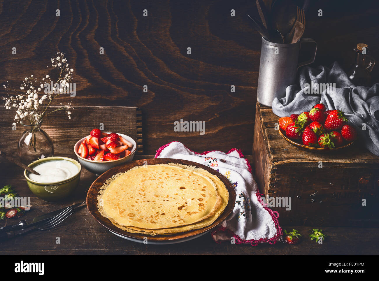 Homemade crepes on dark rustic kitchen table with strawberries and yogurt in bowls . Country style food still life - Stock Image