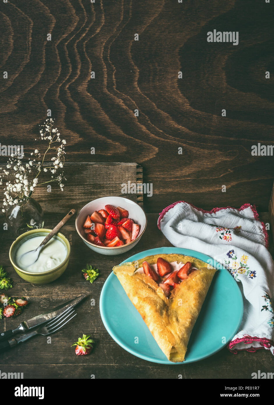Homemade crepes on dark rustic kitchen table with strawberries and yogurt . Country style food still life - Stock Image