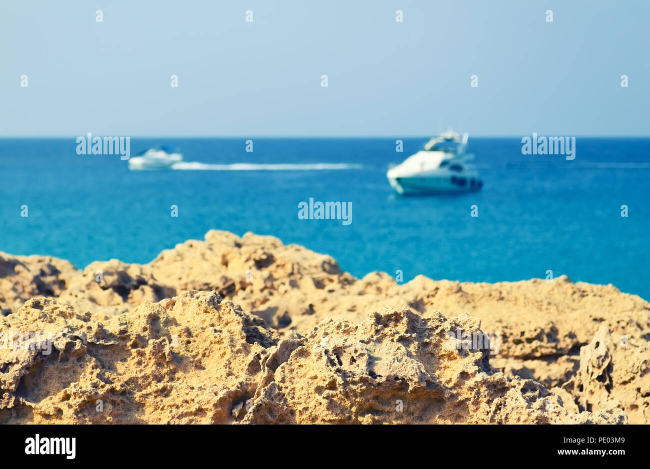 Volcanic rock on a blurred background of the blue sea and boats - Stock Image