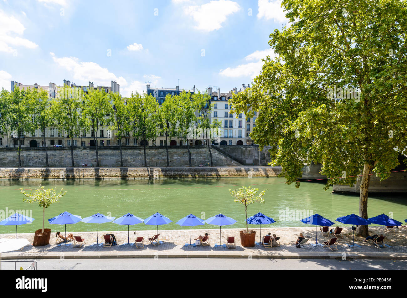 The banks of the Seine with deck chairs and parasols during Paris-Plages summer event in Paris, France, with the Ile de la Cite in the background. - Stock Image