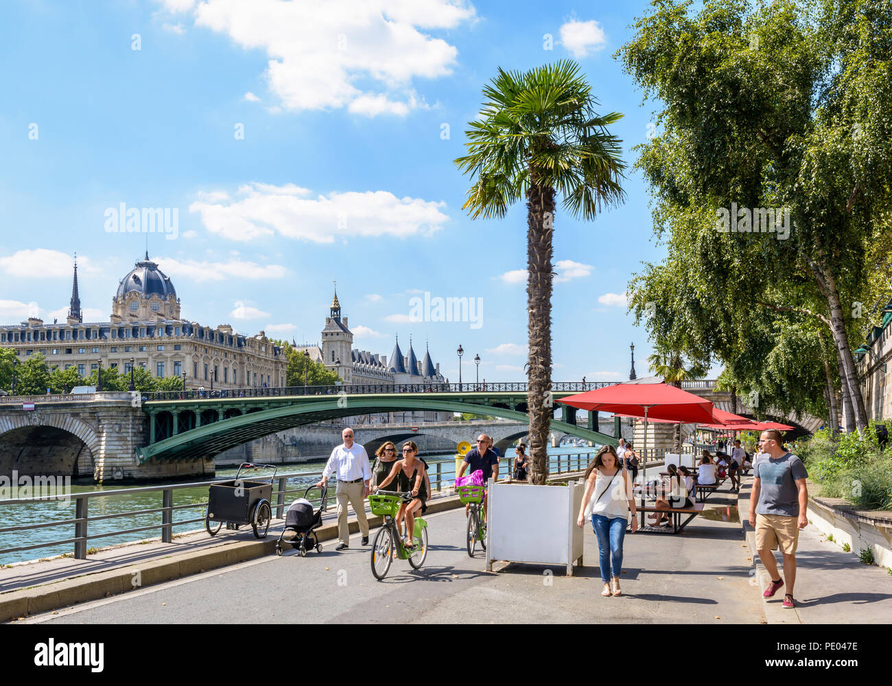 People strolling and biking on the banks of the Seine during Paris-Plages event, with the commercial court and the Palais de la Cite in the background - Stock Image