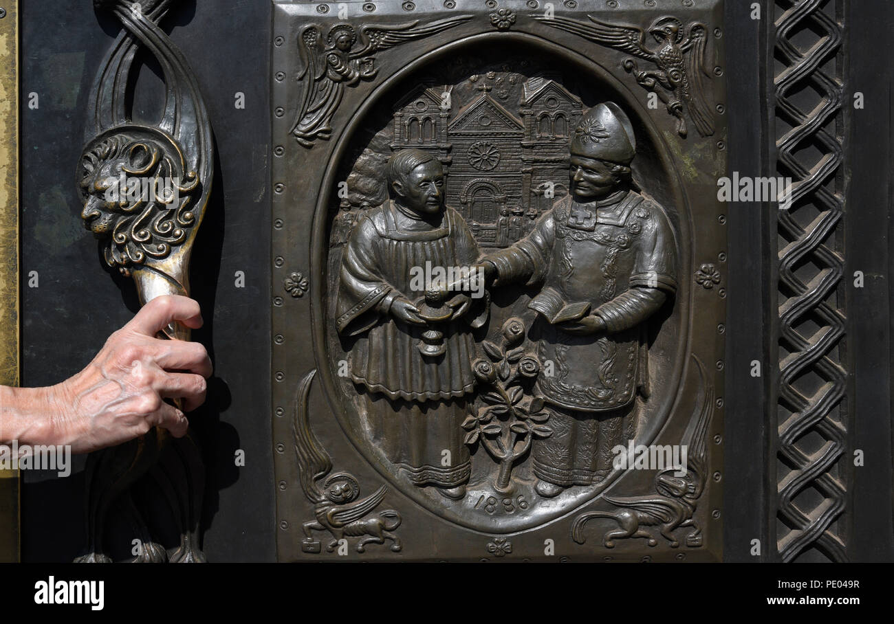 A woman opens the massive bronze entrance doors at the Cathedral Basilica of St. Francis of Assisi in Santa Fe, New Mexico. - Stock Image