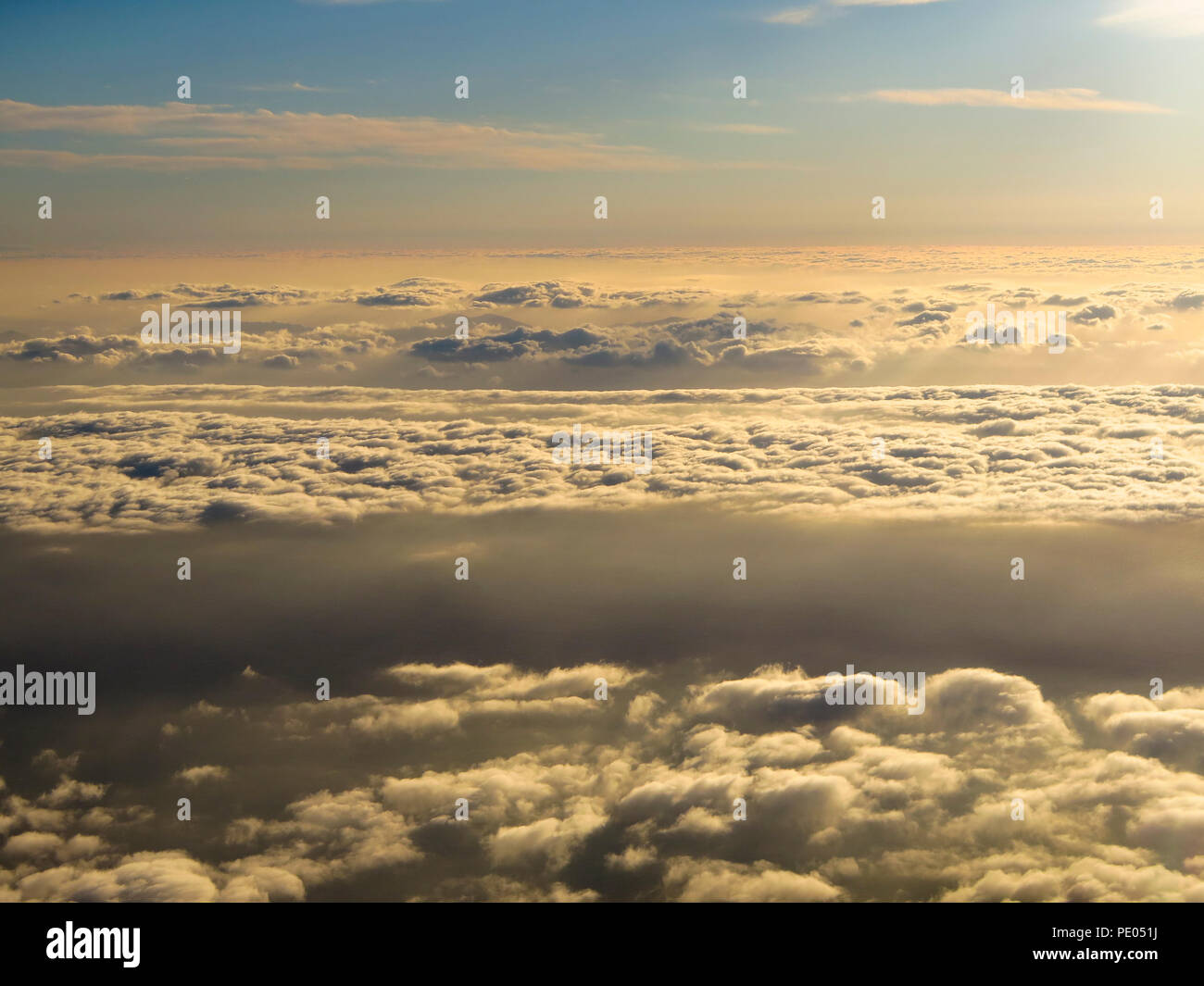 Cloudscape from aeroplane window before sunset - Stock Image