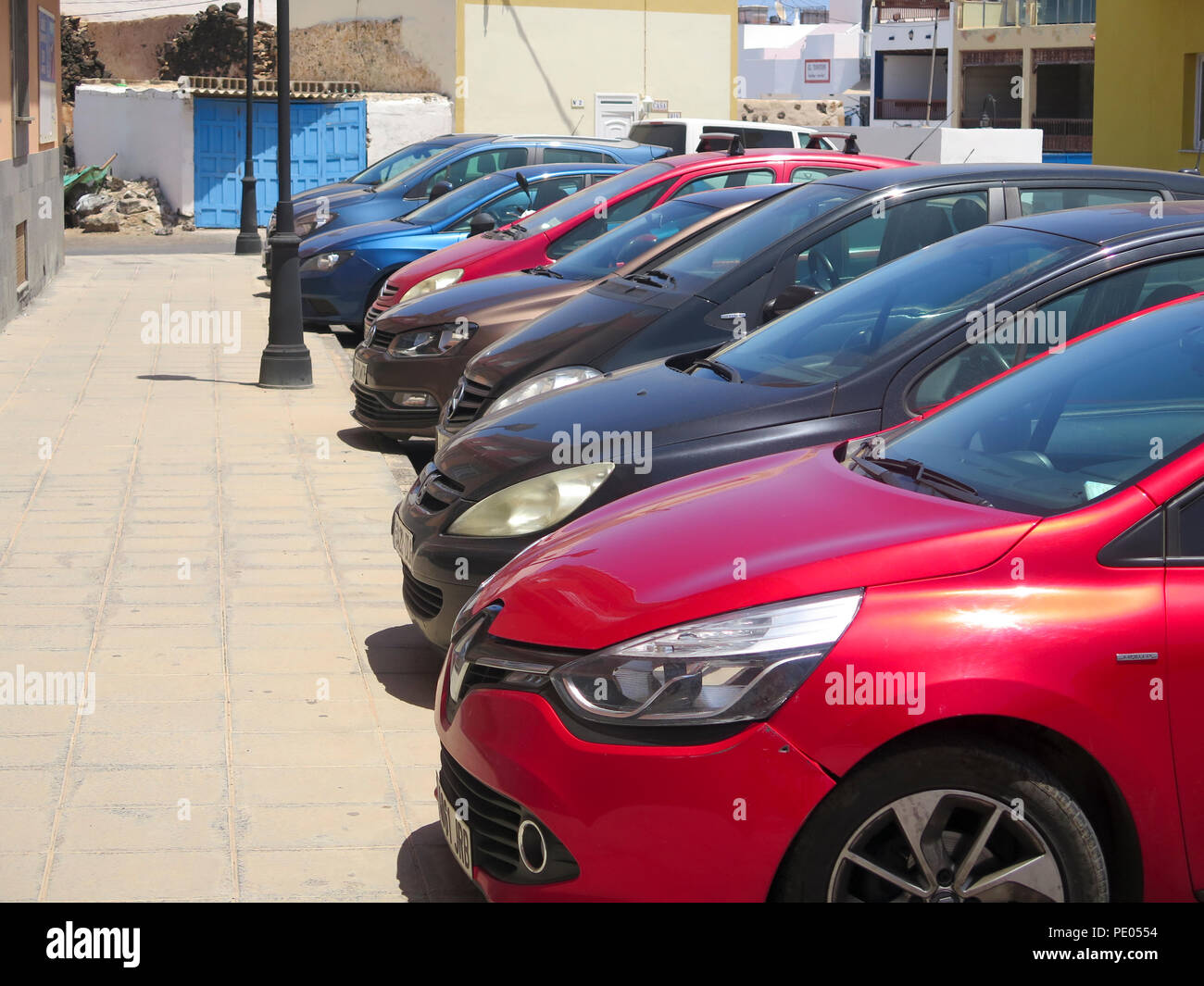 Row of small hatchback cars parked at side of street in bright sun - Stock Image