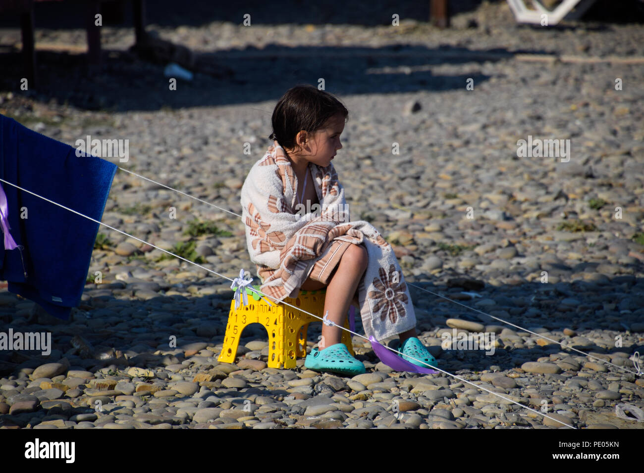 Novorossiysk, Russia - August 06, 2018: The girl sits on a chair near a tent wrapped in a blanket. Stock Photo