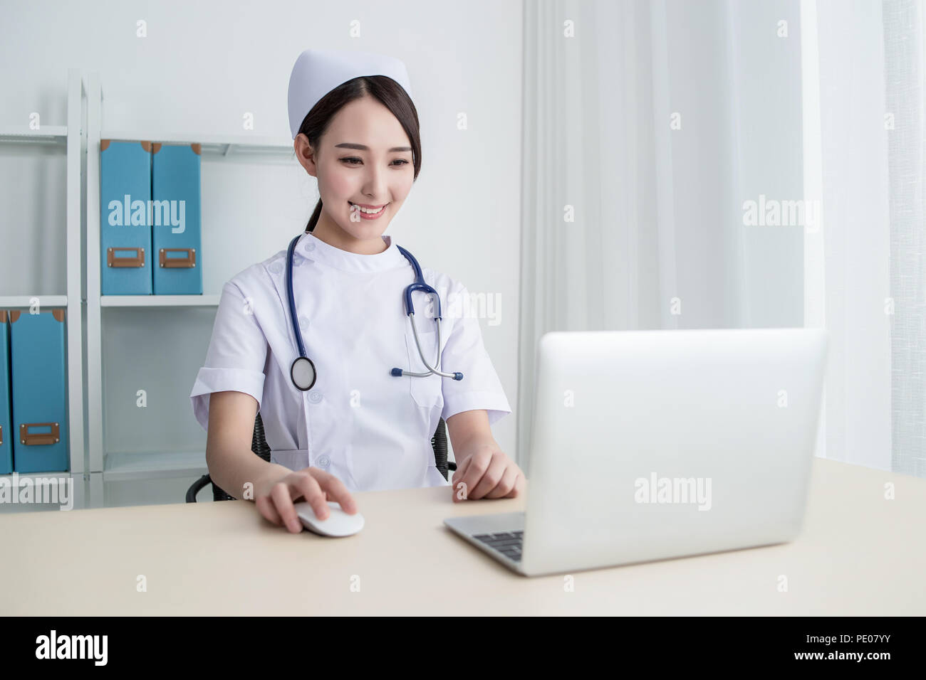 Side view of young female nurse using computer at desk in clinic - Stock Image