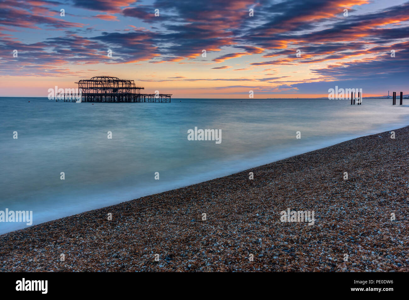 The old destroyed West Pier in Brighton, UK, after sunset - Stock Image