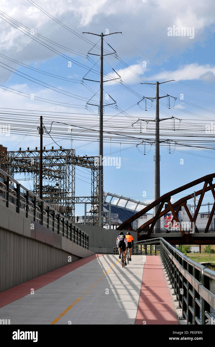 Bike riders ride along the path near the power plant and Invesco Field in Denver.  Exclusive Denver stock photos - Stock Image