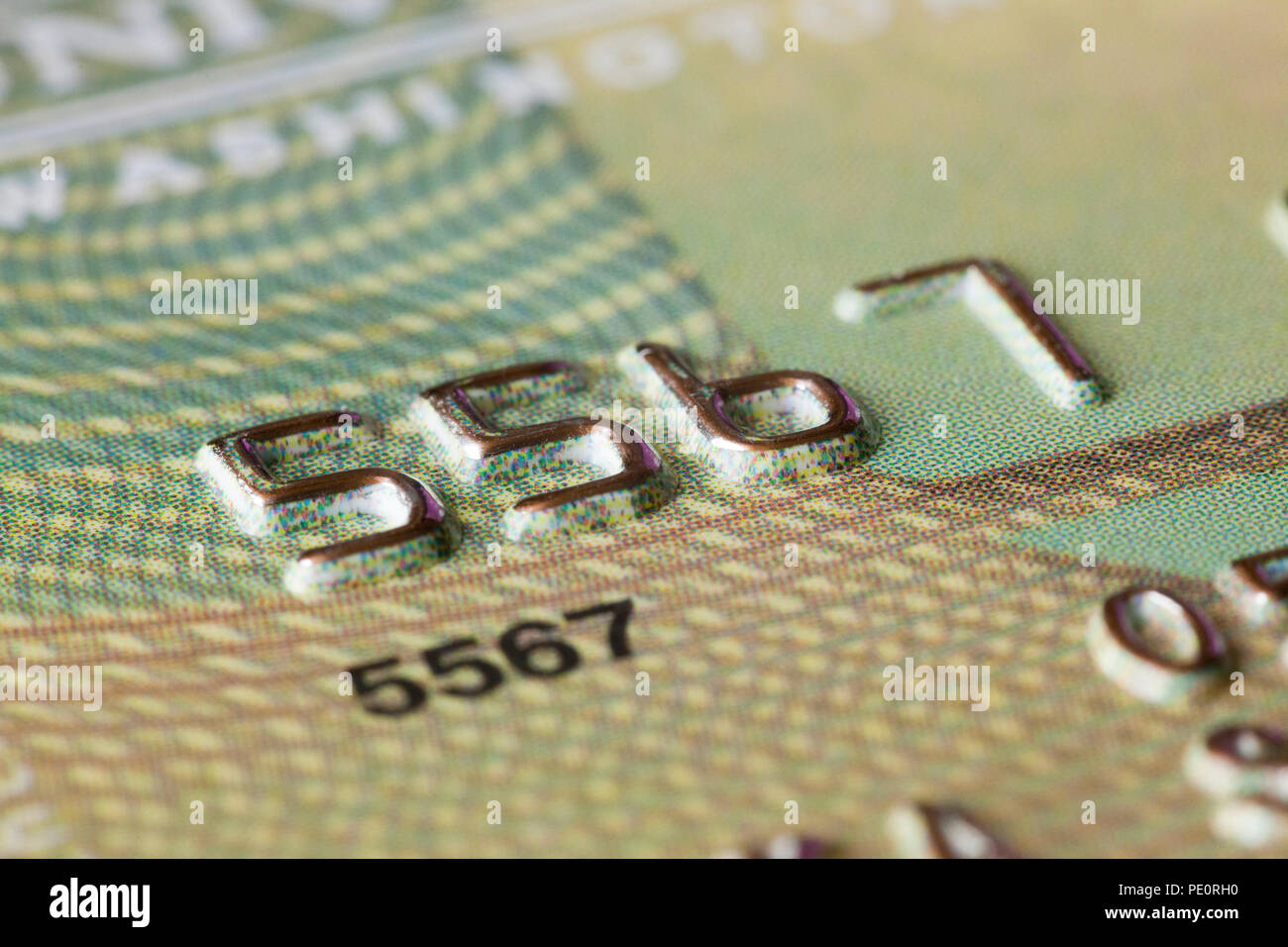 Embossed numbers on credit card close up - USA - Stock Image