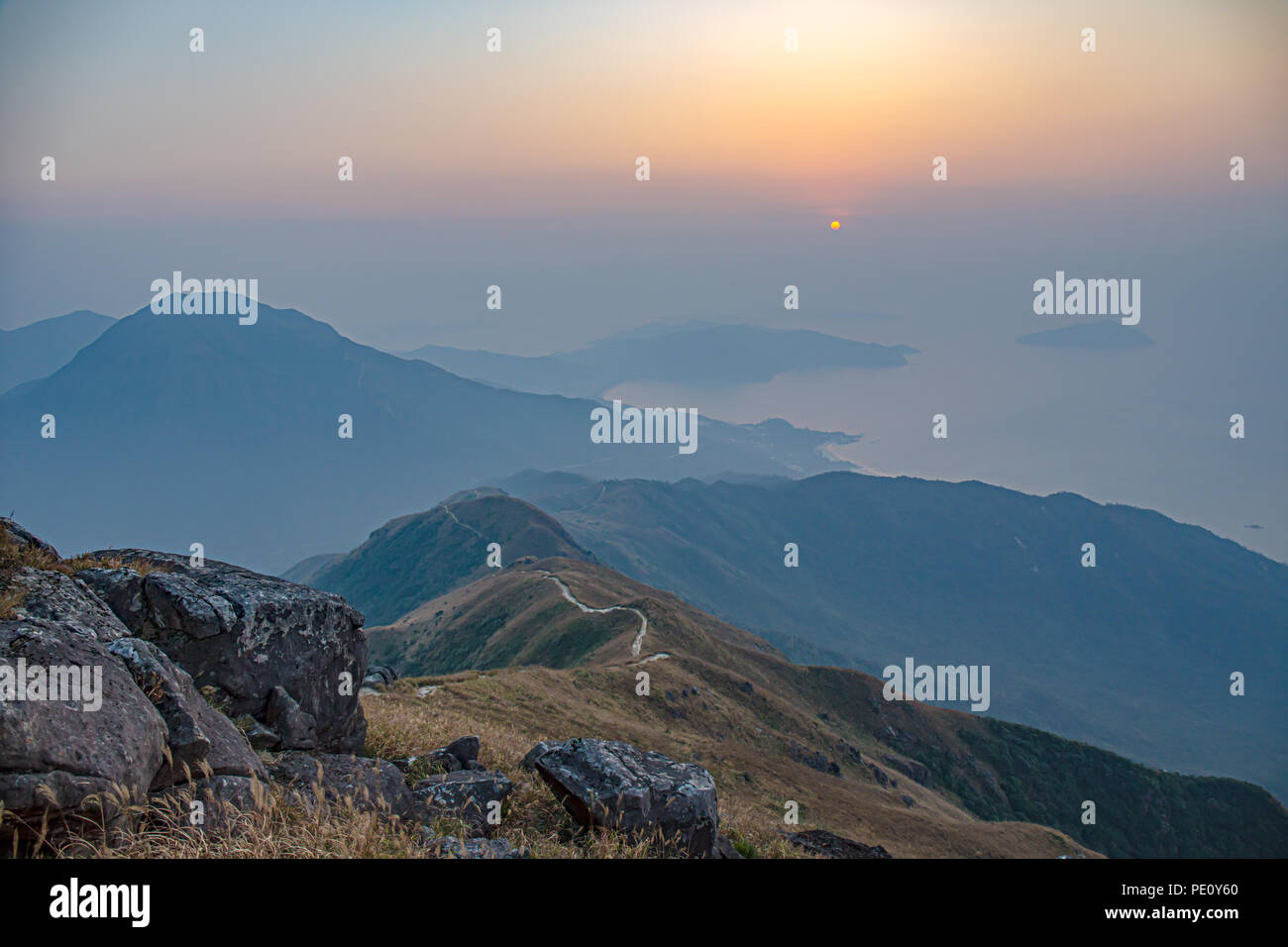 sea, mountain range and hiking trail view from lantau peak, Lantau island, Hong Kong at sunrise in winter season with copy space - Stock Image