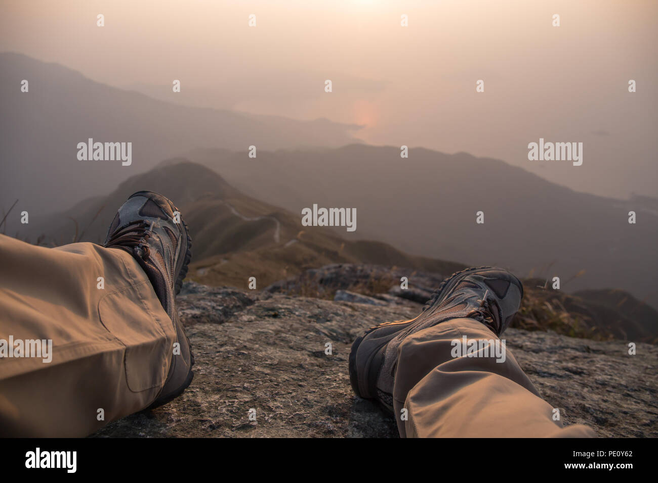 feet and leg of hiker sit on peak with hiking trail and mountain range background with fog at sunrise in winter, Lantau Peak, Hong Kong - Stock Image