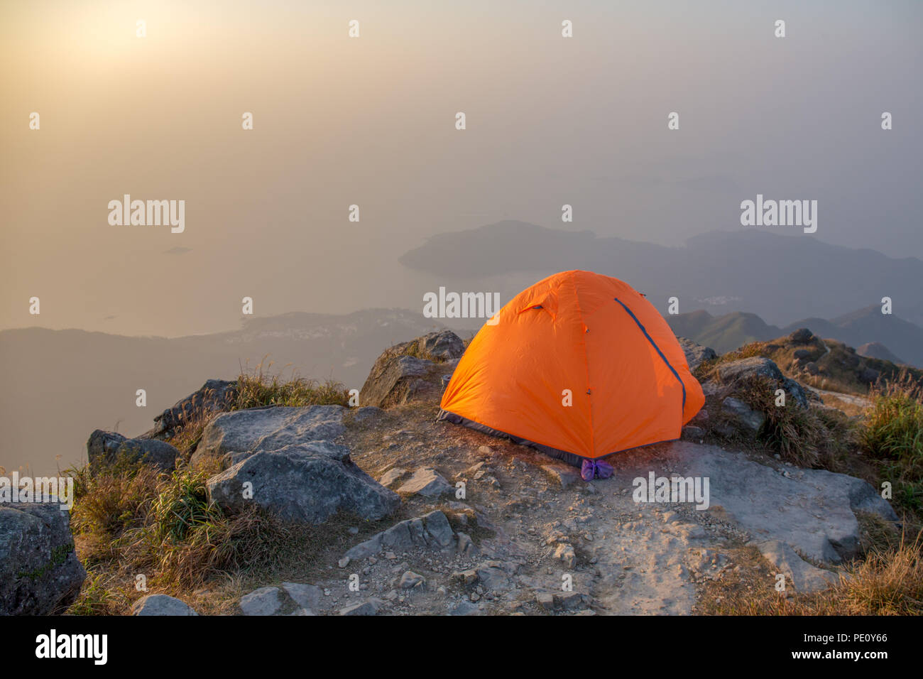 orange tent camping near cliff isolated on lantau peak, Hong Kong in sunrise and fog with copy space - Stock Image