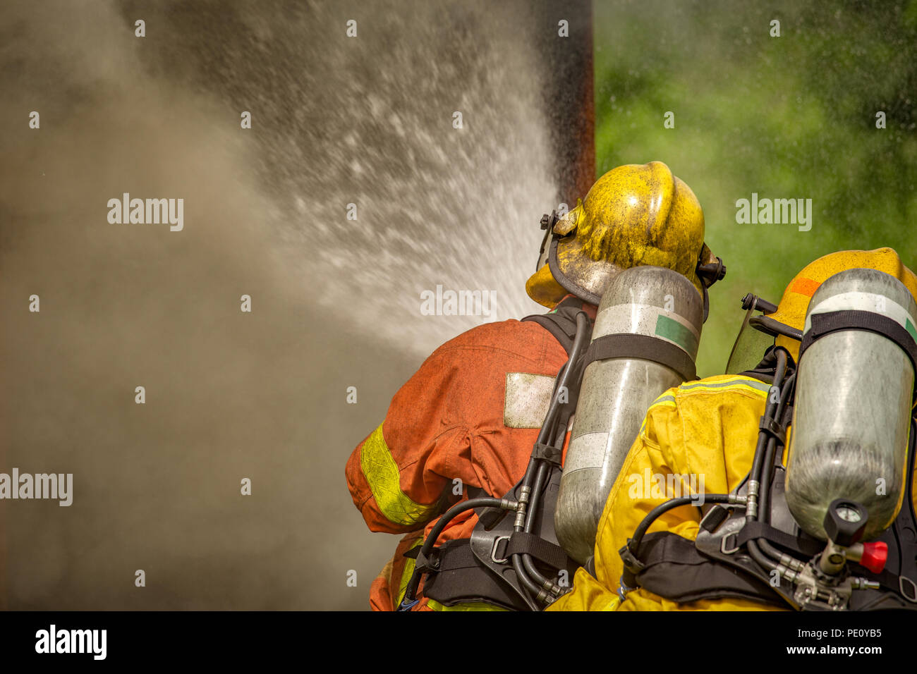 close up action of two firefighters water spray by high pressure nozzle to fire and  smoke with  copy space in cinematic tone - Stock Image