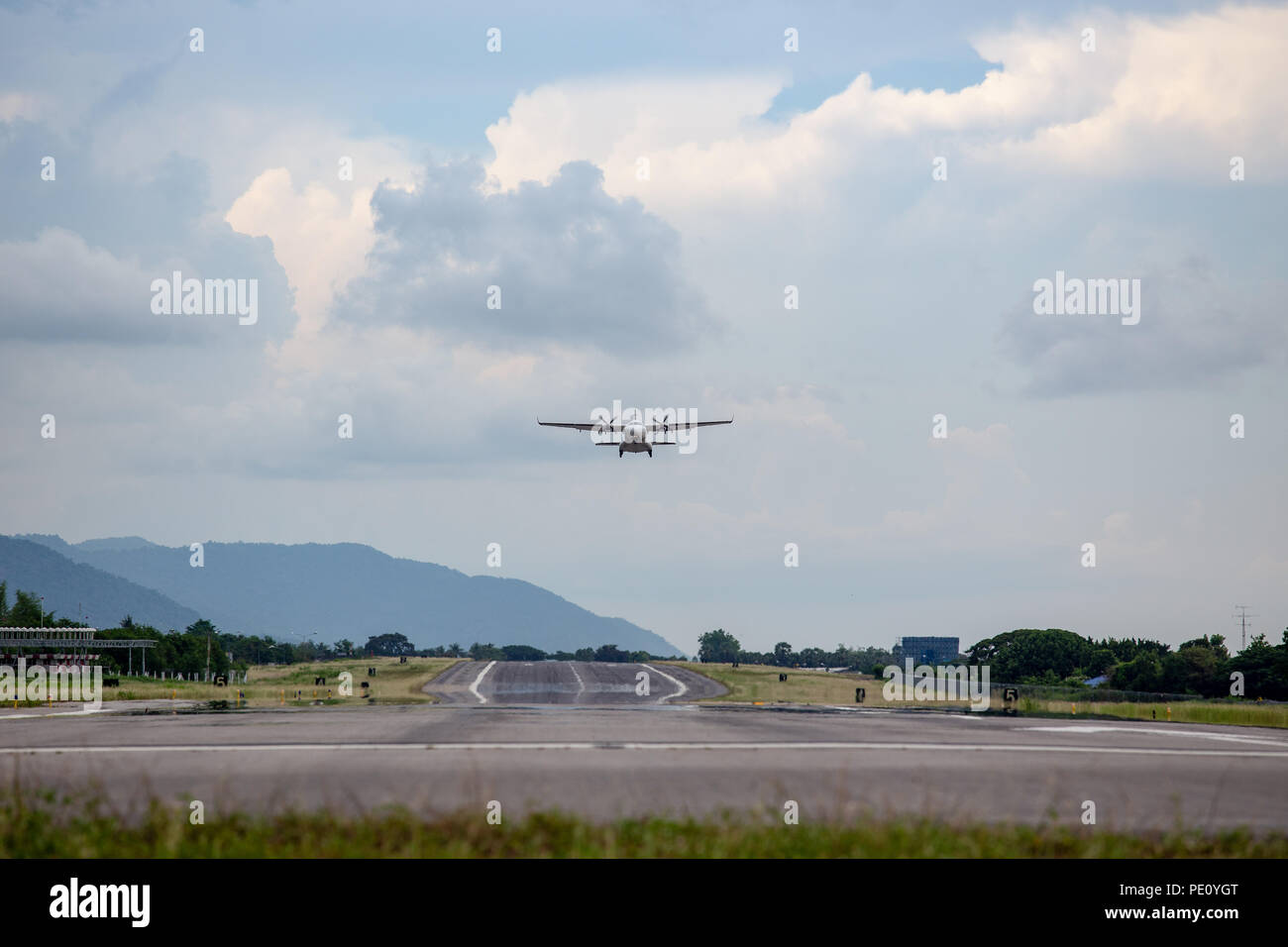 twin engines propeller aircraft take off from runway and climb with cloud and sky background and copy space - Stock Image