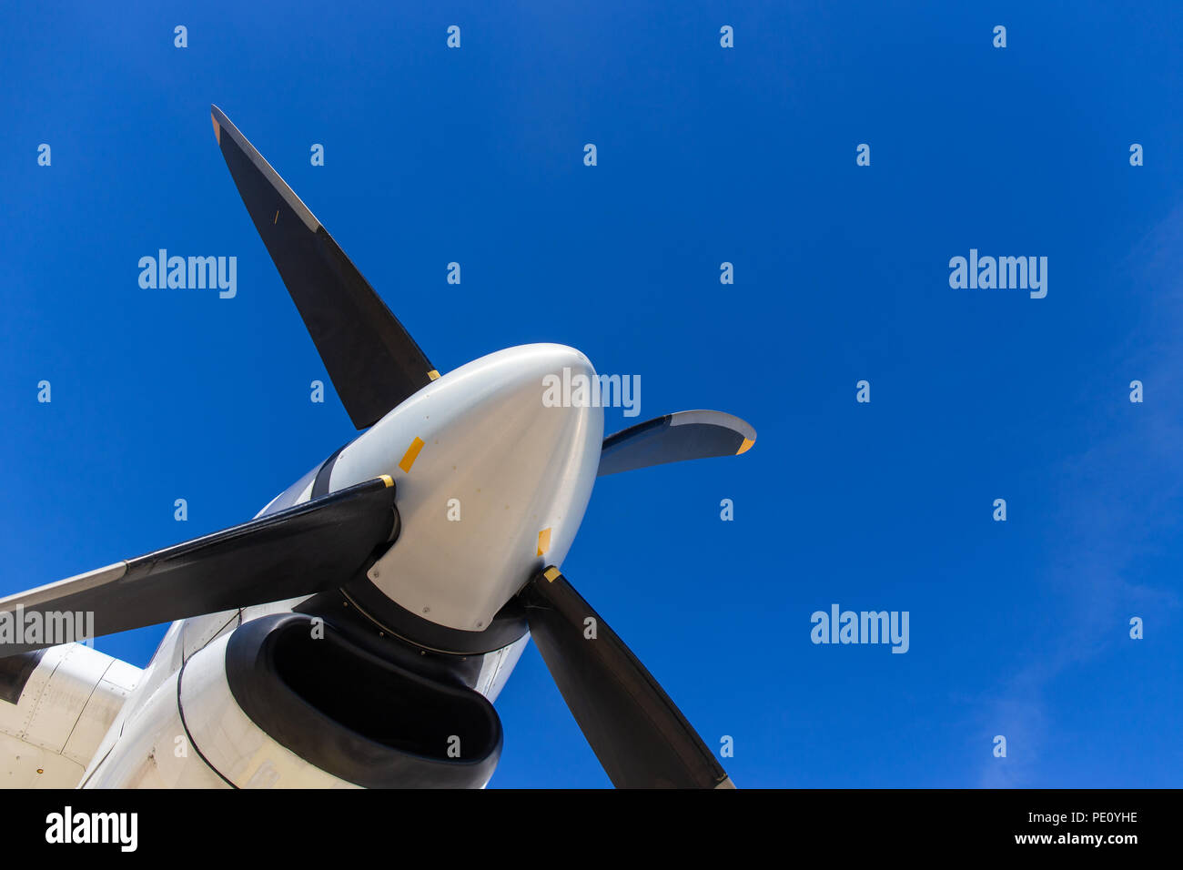 bottom view of aircraft propeller blade and turboprop engines with blue sky background and copy space - Stock Image