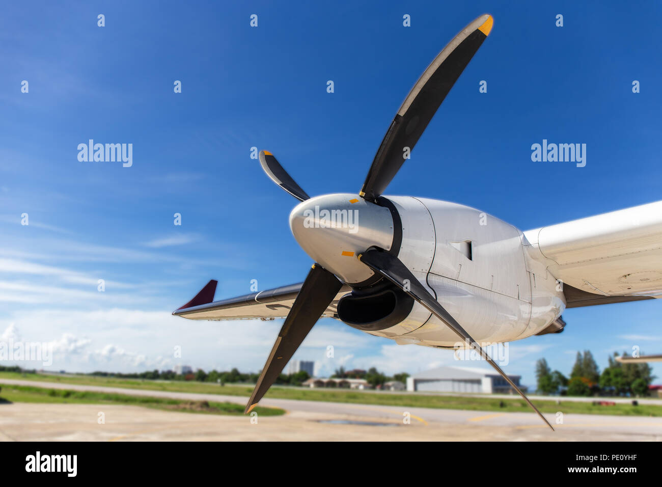aircraft propeller blade and turboprop engines with airfield, blue sky background and copy space - Stock Image