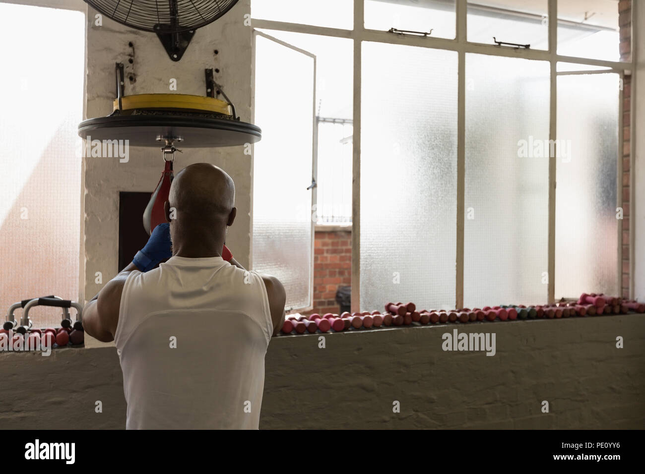 Man punching the speed bag in the fitness studio - Stock Image