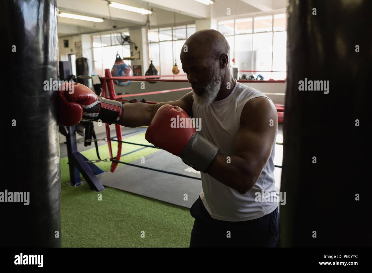 Senior man practicing boxing on the punching bag - Stock Image
