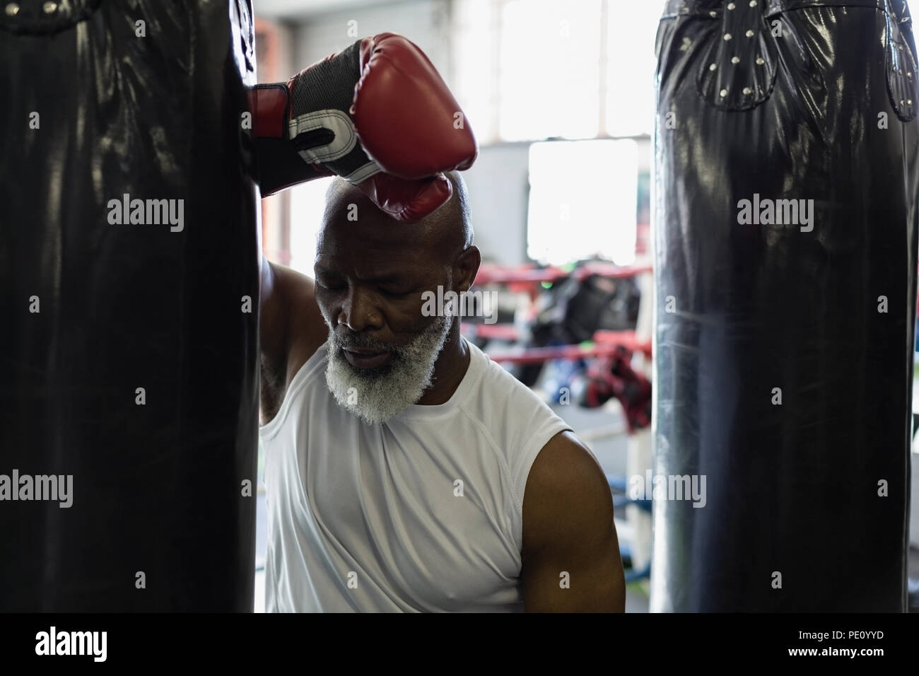 Tired senior boxer leaning against the punching bag - Stock Image