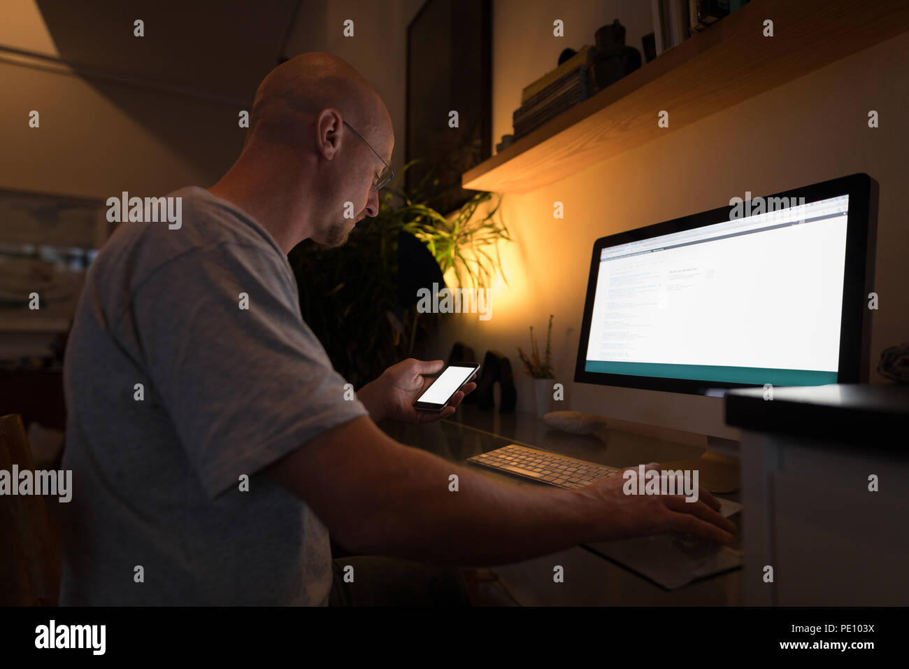 Man working on personal computer while using mobile phone - Stock Image