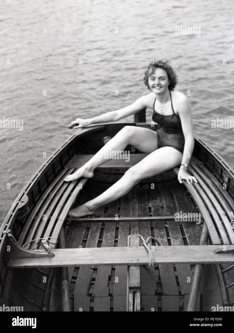 Attractive young lady sitting in rear of small dinghy - Stock Image