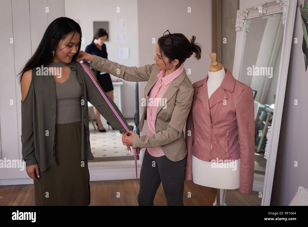 Fashion designer measuring the lengths of a customer - Stock Image