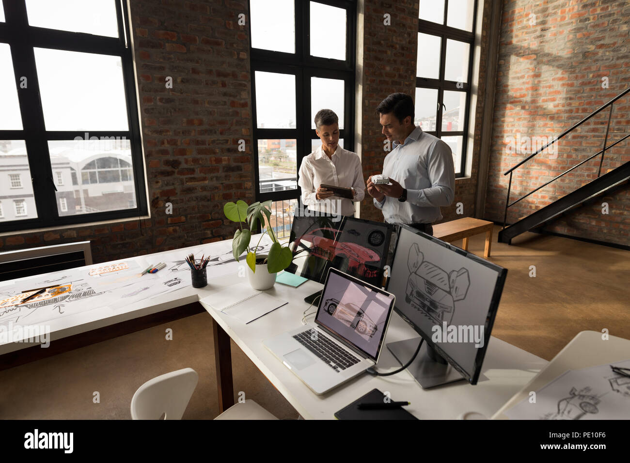 Business colleagues discussing over digital tablet - Stock Image