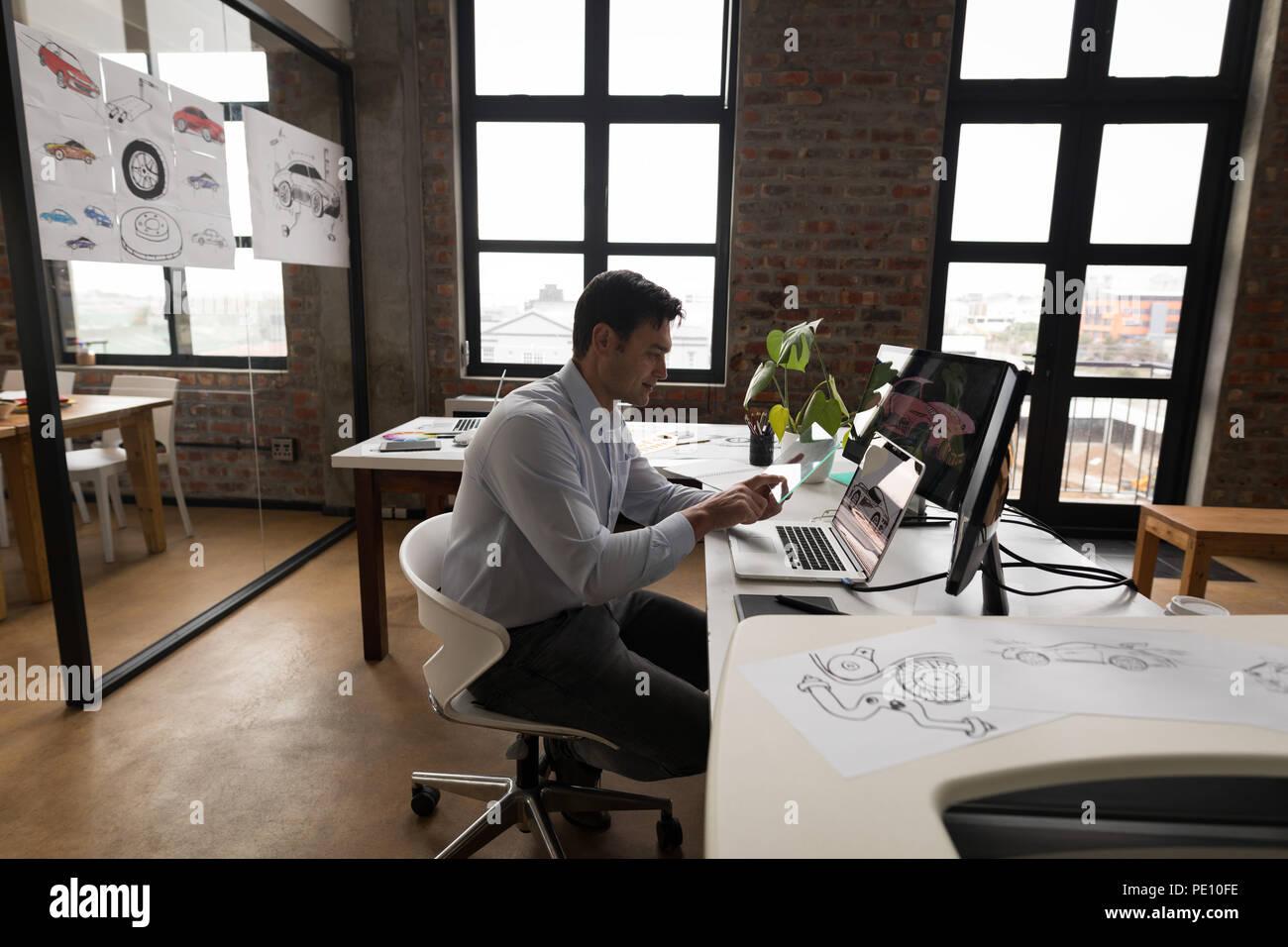 Businessman using glass digital tablet at desk - Stock Image