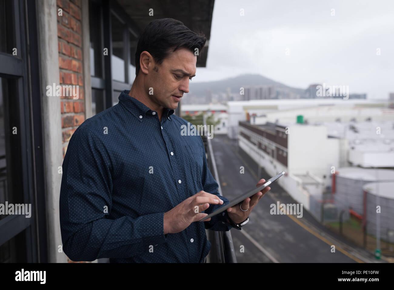 Businessman using digital tablet in balcony - Stock Image