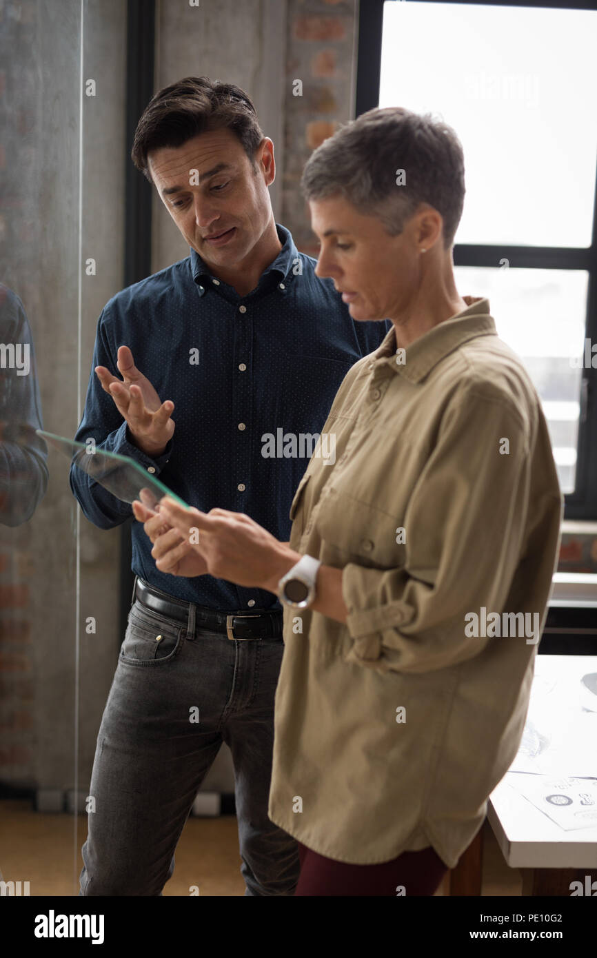 Business colleagues discussing over glass digital tablet - Stock Image