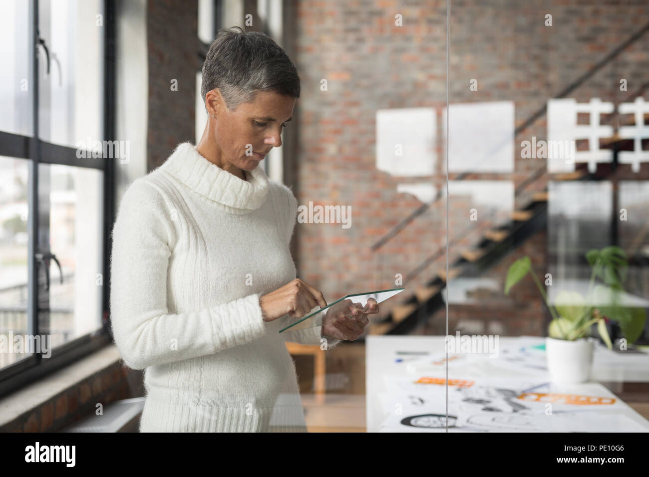 Businesswoman using glass digital tablet - Stock Image