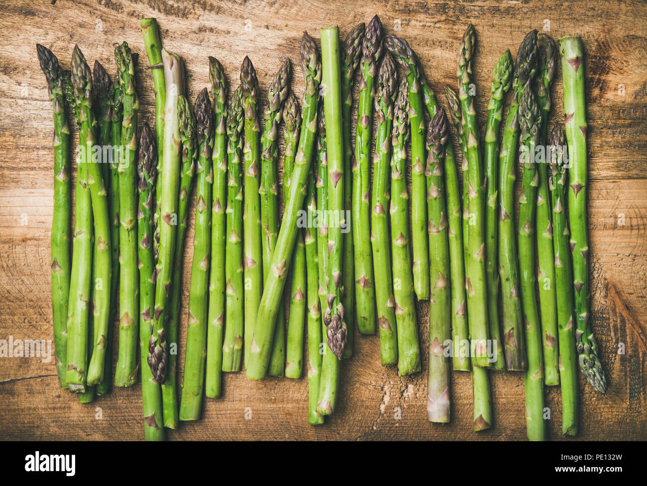 Raw uncooked green asparagus in row over wooden background - Stock Image
