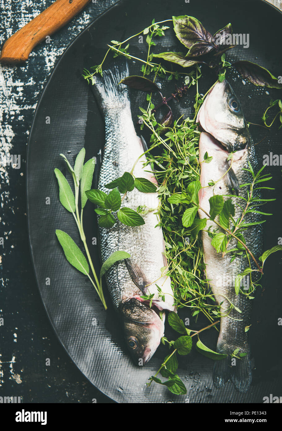 Flat-lay of raw uncooked sea bass fish with herbs - Stock Image