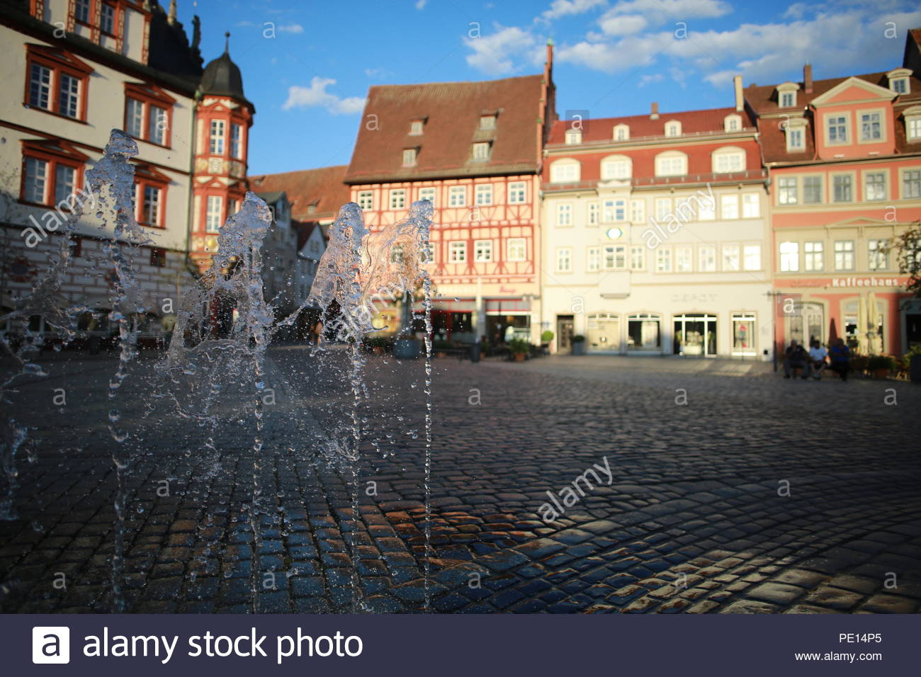 Jets of water shoot into the air in the market square in the town of Coburg, Germany on a beautiful summer's evening during a heat wave - Stock Image