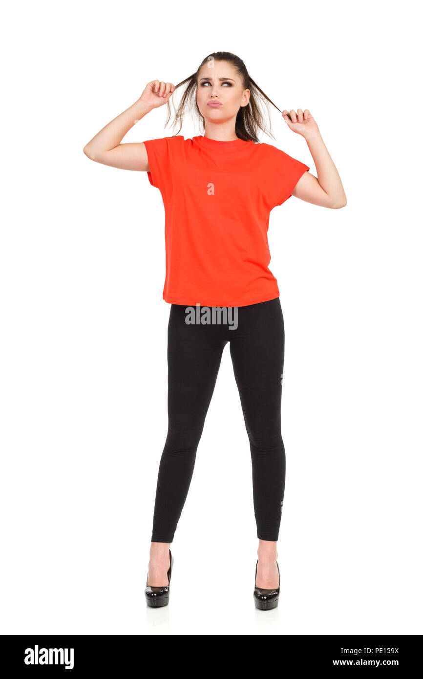 Grimacing young woman in black leggings, high heels and orange shirt is standing, holding her hair and looking away. Full length studio shot isolated  - Stock Image