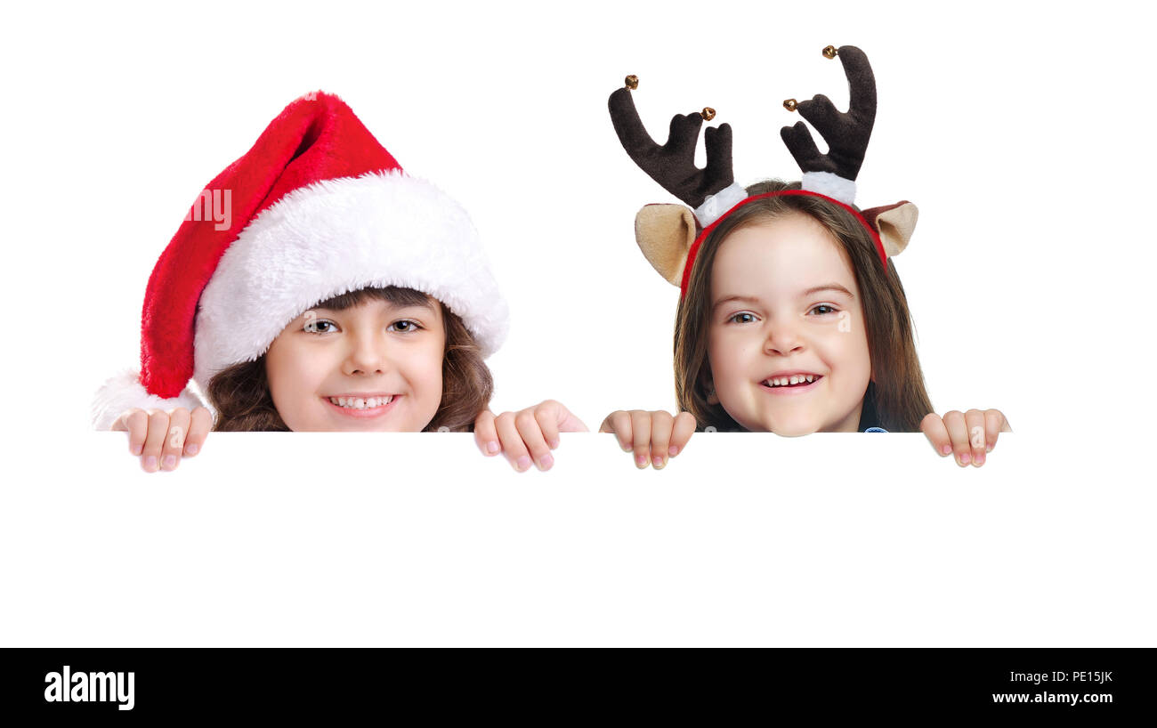 Two girls wearing christmas hats holding the blank board - Stock Image