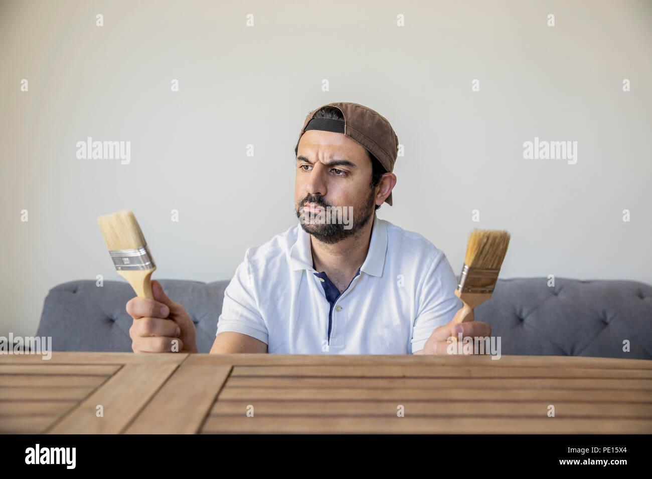 arab man choosing a pint brush to renovate a teak wood table - Stock Image
